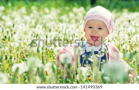 Beautiful happy little baby girl sitting on a green meadow with white flowers dandelions on the nature in the park - stock photo