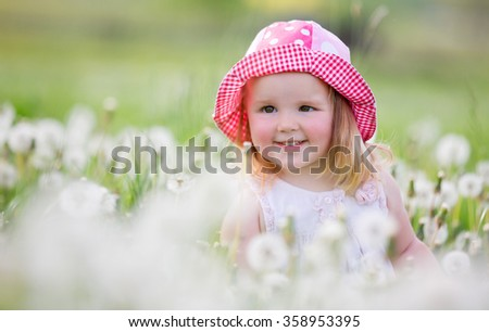 Beautiful happy little baby girl wearing red white dotted hat sitting on a green meadow with white flowers dandelions on the nature. - stock photo