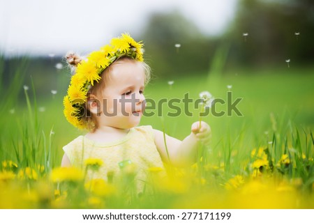 Beautiful happy little baby girl with a wreath on a meadow between yellow flowers dandelions - stock photo