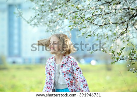 Beautiful happy little girl  enjoying smell in a flowering spring garden - stock photo