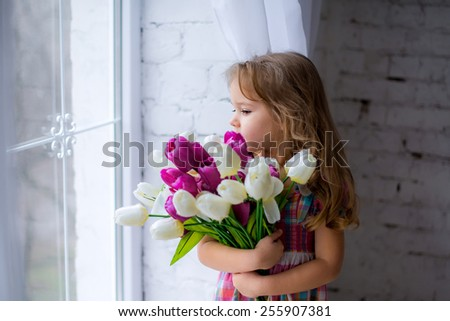 beautiful happy little girl in the window at home with tulips
