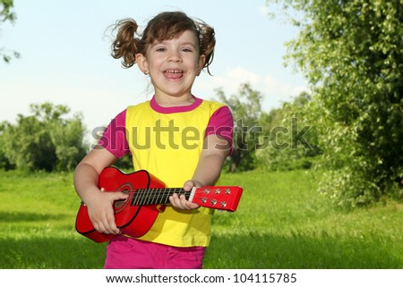 beautiful happy little girl play guitar and sing - stock photo