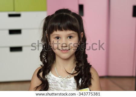Beautiful happy little girl reading a book in the room - stock photo