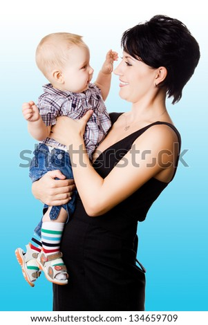 Beautiful happy mather with attractive baby boy o. Portrait of  baby and his mother. - stock photo