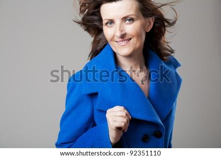 Beautiful happy mature woman posing on gray background. - stock photo