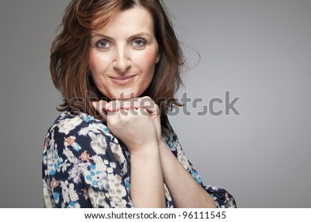 Beautiful happy middle age woman posing in studio. - stock photo