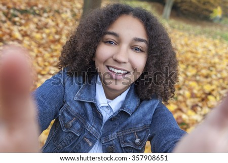 Beautiful happy mixed race African American girl teenager female child smiling with perfect teeth taking selfie photograph  - stock photo