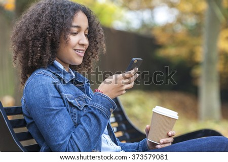 Beautiful happy mixed race African American girl teenager female young woman smiling drinking takeaway coffee and cell phone texting sitting on a park bench in autumn or fall - stock photo