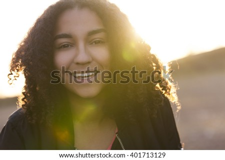 Beautiful happy mixed race African American girl teenager female young woman with perfect teeth smiling in golden light with sun flare at sunset or sunrise - stock photo