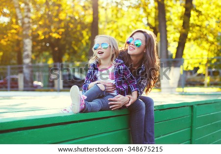 Beautiful happy mother and child daughter having fun together in city park - stock photo