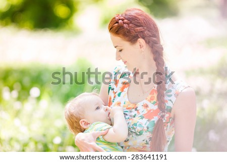 Beautiful happy mother breastfeeding her baby boy outdoor - stock photo
