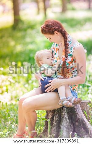 Beautiful happy mother breastfeeding her baby boy outdoor - stock photo