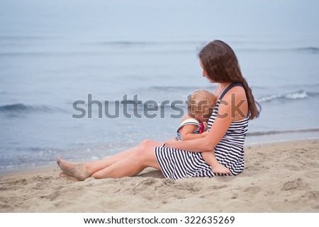 Beautiful happy mother breastfeeding  small child on  sea shore, italy  - stock photo