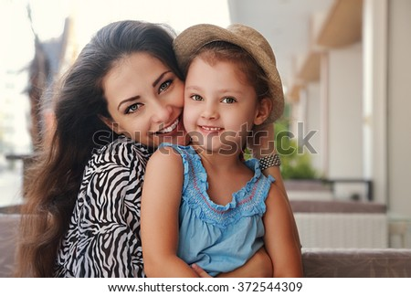 Beautiful happy mother hugging her joying smiling daughter indoor background - stock photo