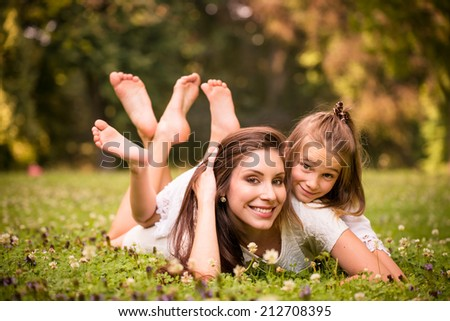 Beautiful happy mother lying down on grass with her girl - outdoor in nature - stock photo