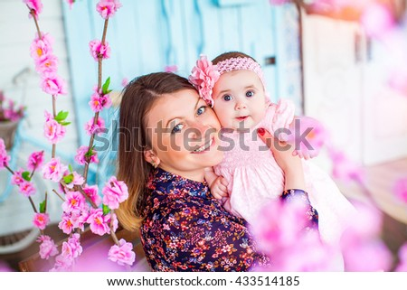 Beautiful happy mother with adorable daughter cute smiling girl holding on hands on background of cherry blossoms. Happy childhood. Background, macro, closeup - stock photo