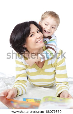 Beautiful happy mother with child 4 years boy reading book isolated on white
