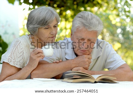 Beautiful happy old couple with drink and book in summer - stock photo
