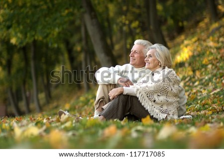 beautiful happy old people sitting in the autumn park - stock photo