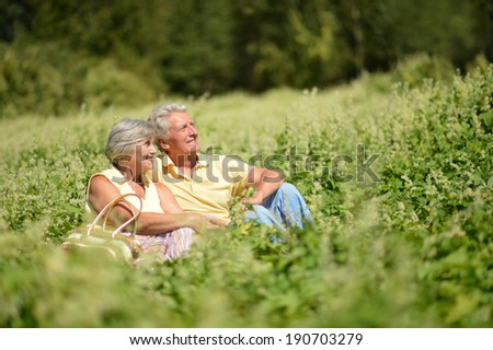 Beautiful happy old people sitting in the summer park