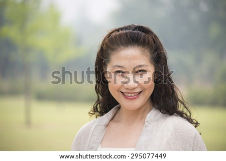 Beautiful happy older woman smiled looking at camera - stock photo