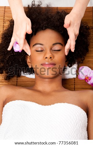 Beautiful happy peaceful sleeping Brazilian woman at day spa, laying on bamboo table with head on pillow wearing a towel getting a facial temple massage, isolated. - stock photo