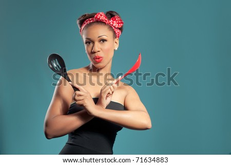 Beautiful happy pin-up style housewife with kitchen utensils, retro style studio portrait - stock photo