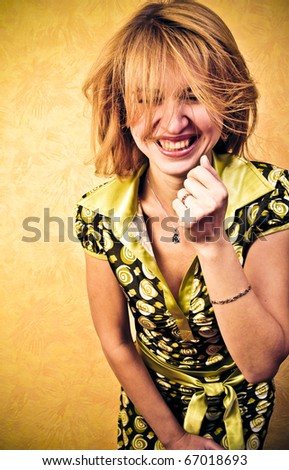 Beautiful happy portrait of an young adult blonde woman against orange wall - stock photo