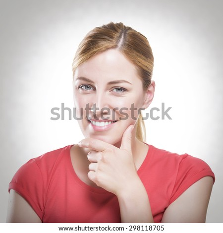 Beautiful happy portrait of an young adult smiling blonde woman holding her chin - toned photo. - stock photo