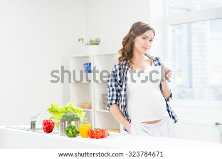 Beautiful happy pregnant woman having a cup of coffee. - stock photo