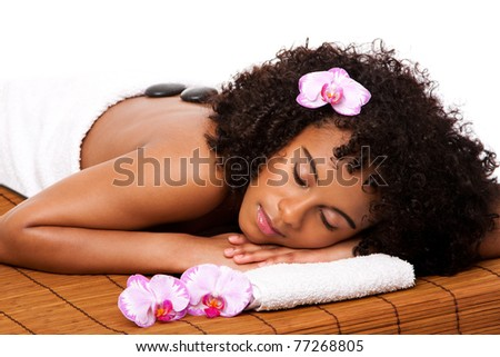 Beautiful happy relaxed Brazilian Latina-African woman at health day spa with hot stone massage treatment laying in white towel on bamboo table decorated with orchids. - stock photo