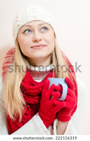 Beautiful happy romantic smiling blue eyes young woman wearing red knitted gloves and shawl holding cup of hot drink - stock photo