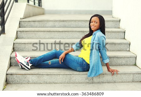 Beautiful happy smiling african woman wearing a jeans clothes sitting resting on stairs