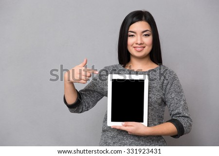 Beautiful happy smiling asian girl in gray jumper looking at camera staying and pointing on tablet computer - stock photo