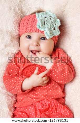 Beautiful  happy smiling baby girl in funny hat lying on blanket, studio shot - stock photo