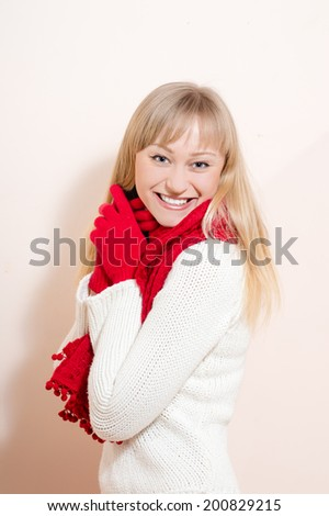 Beautiful happy smiling blond young woman with great whitening dental care teeth wearing knitted red scarf and gloves looking at camera on white or light wall copy space background portrait image