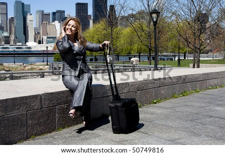 Beautiful happy smiling Caucasian Latina entrepreneur business woman in grey suit sitting in park in New York City talking on cell phone with a carry-on luggage and purse.