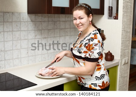Beautiful happy smiling Caucasian woman in kitchen interior with chicken - stock photo