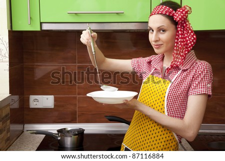 Beautiful happy smiling cooking woman in kitchen interior - stock photo
