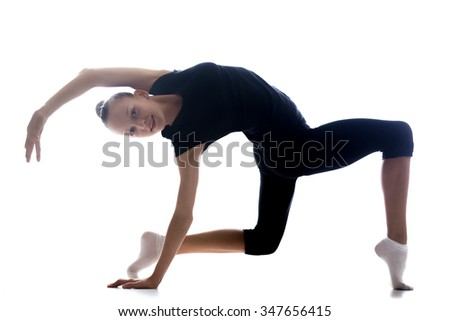 Beautiful happy smiling cool young fit gymnast athlete woman in sportswear doing art gymnastics, standing in backbend acrobatic exercise on tiptoes, full length, studio, dark background - stock photo