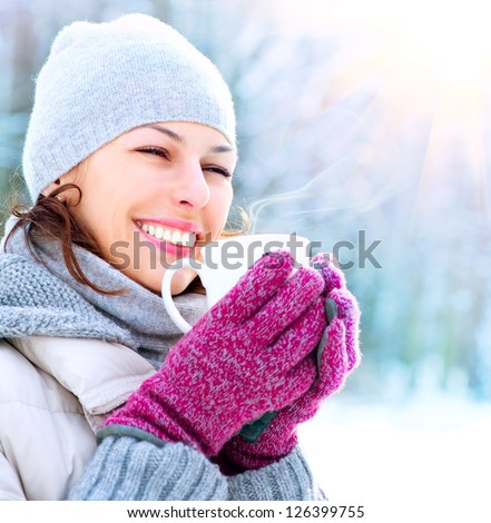 Beautiful Happy Smiling Winter Woman with Mug Outdoor. Laughing Girl Outdoors with Hot Drink - stock photo
