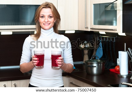 Beautiful happy smiling woman in kitchen interior holding glasses with beverages