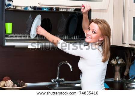 Beautiful happy smiling woman in kitchen interior. One person only - stock photo