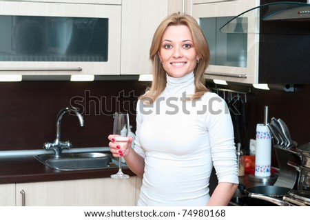 Beautiful happy smiling woman in kitchen interior with glass. One person only