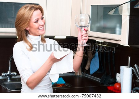 Beautiful happy smiling woman in kitchen interior with glasses. One person only