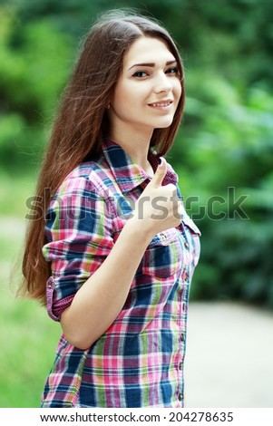 beautiful happy smiling young woman showing thumb up