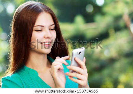 beautiful happy smiling young woman using mobile texting messages - stock photo
