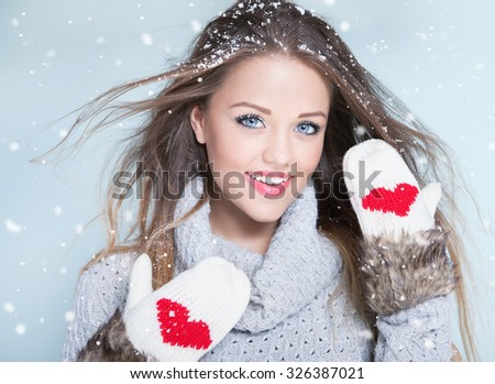 Beautiful happy smiling young woman wearing winter gloves covered with snow flakes. Christmas portrait concept. - stock photo