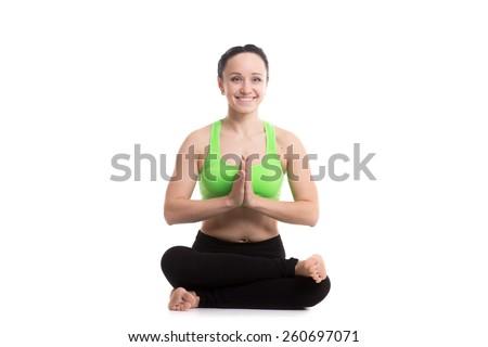 Beautiful happy sporty girl practicing yoga, siting in fire log pose, agnistambhasana, hands in namaste - stock photo