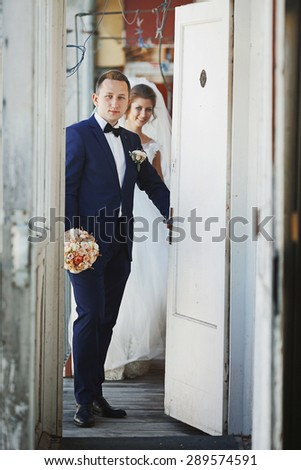 beautiful happy stylish bride with elegant groom  on the background of  white rustic doors - stock photo